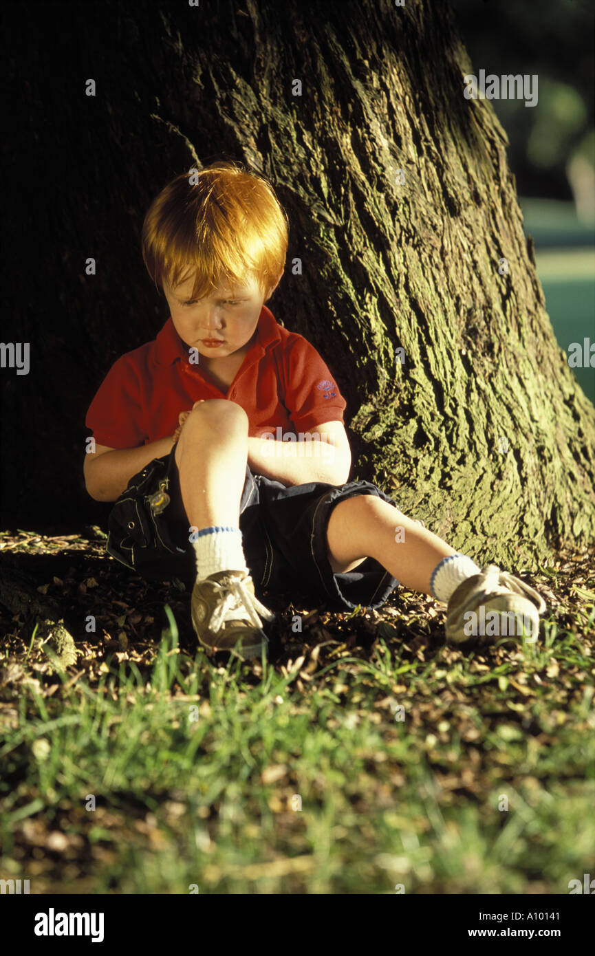Sad Red Haired Little Boy Sitting In Front Of A Tree Stock