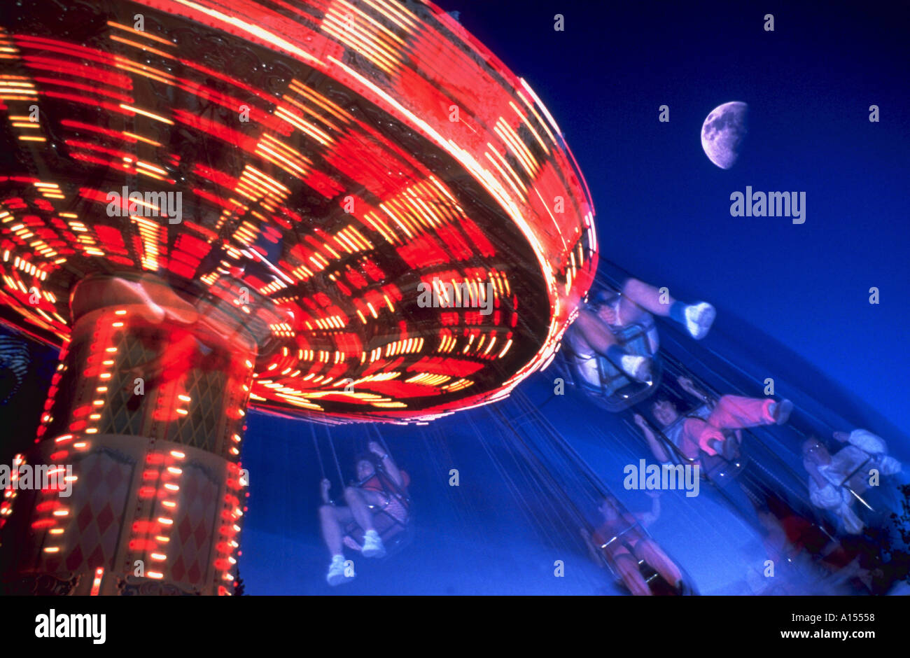 Kids at night with moon royalty free stock photography image - Blurred Image Of Children Riding A Carousel Swing At An Amusement Park With A Half Moon In The Night Sky In The Background Novastock Alamy Stock Photo