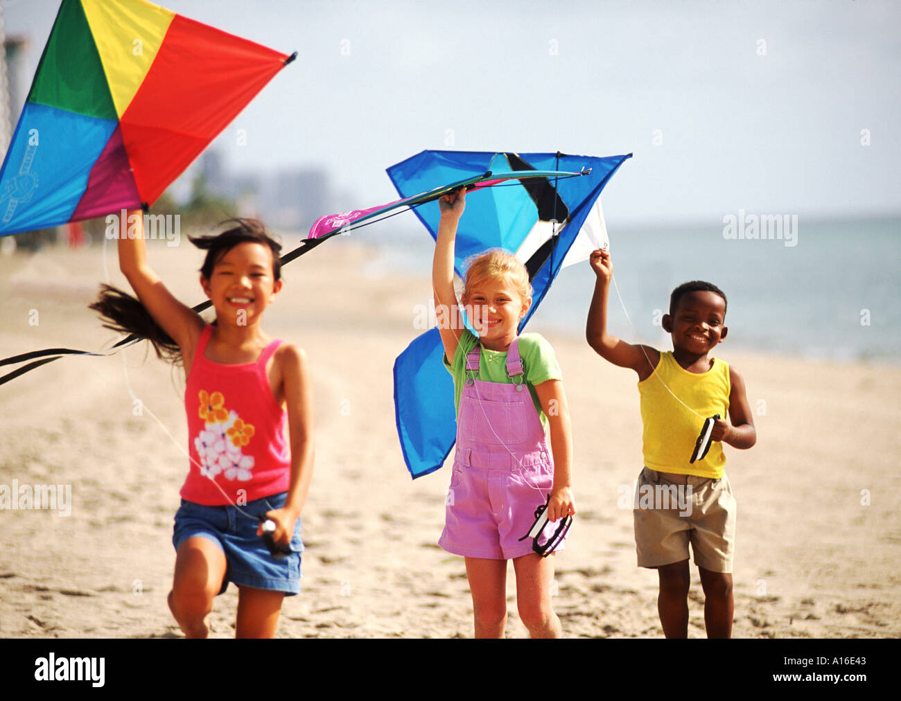 Children Age 6 Flying Kites On The Beach With Mixed Ethnic Kids