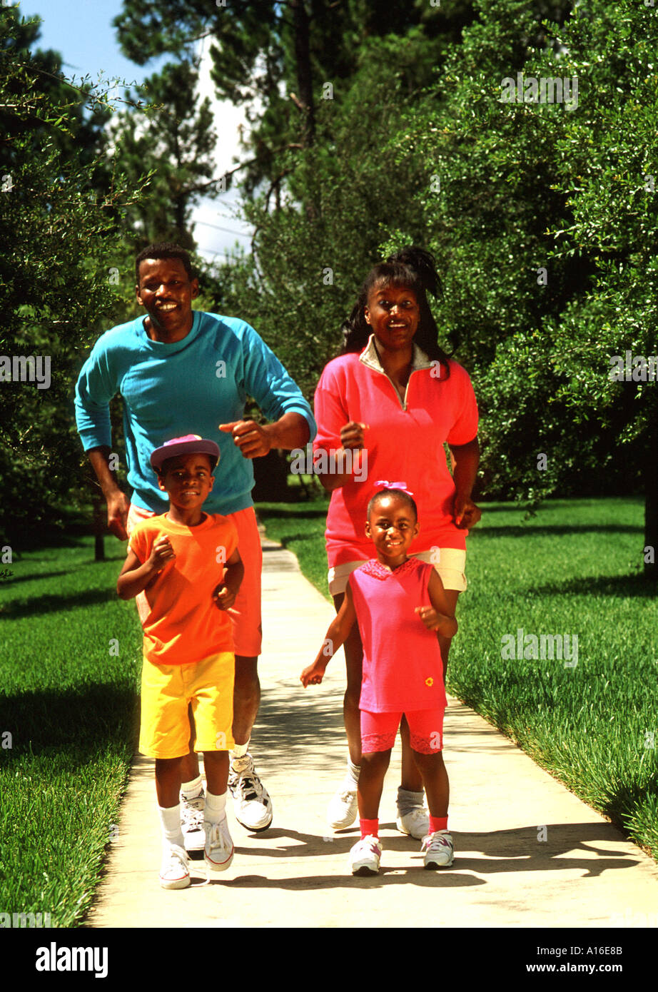 Healthy black family jogging together in park for exercise ...