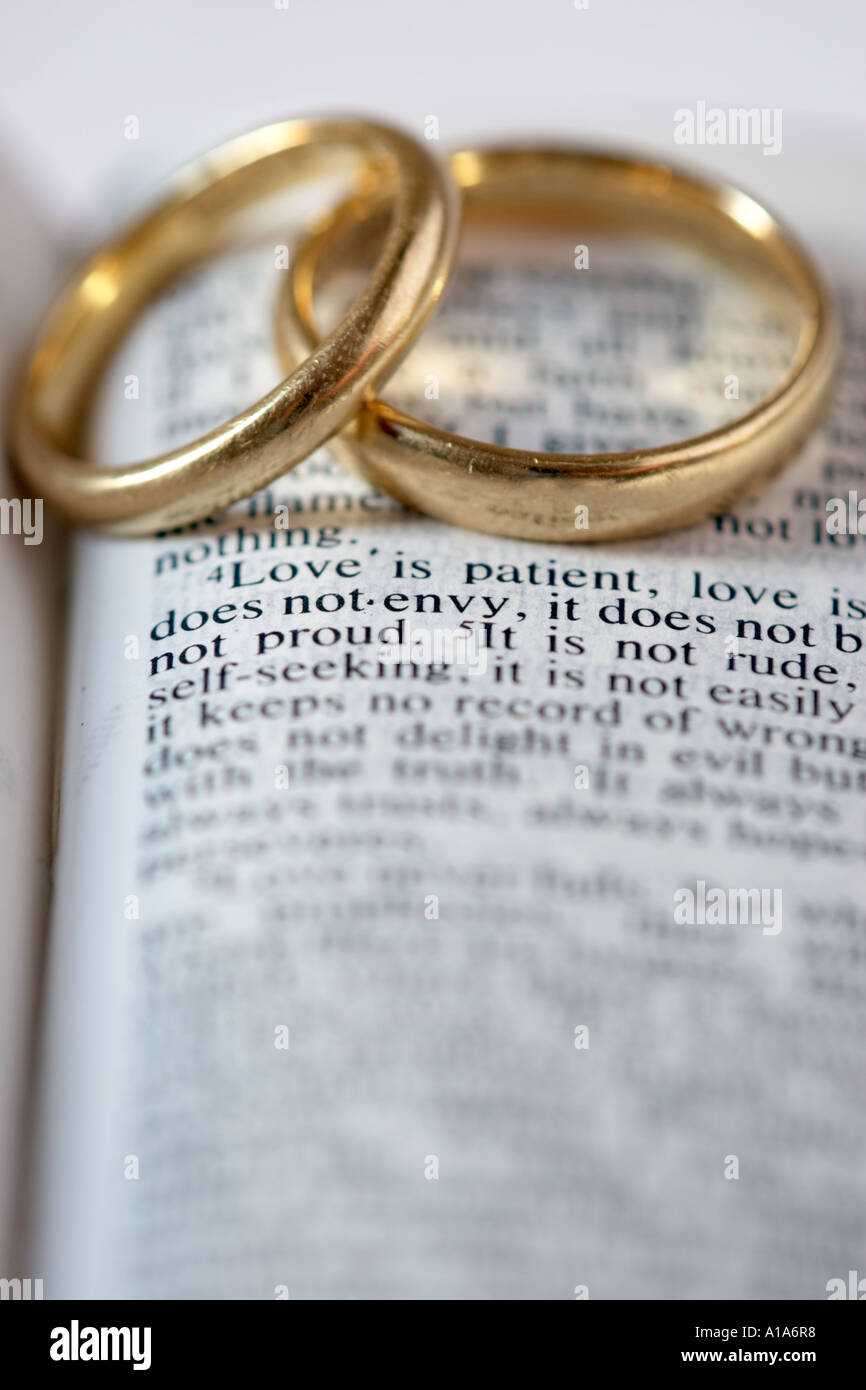 Two gold wedding rings lie on an open bible the verses for Wedding ring meaning bible