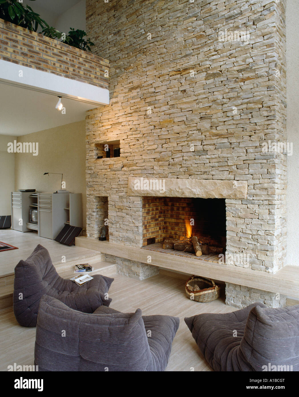 Lit Fire In Fireplace In Stone Wall Of Barn Conversion, With Modern Grey  Armchairs