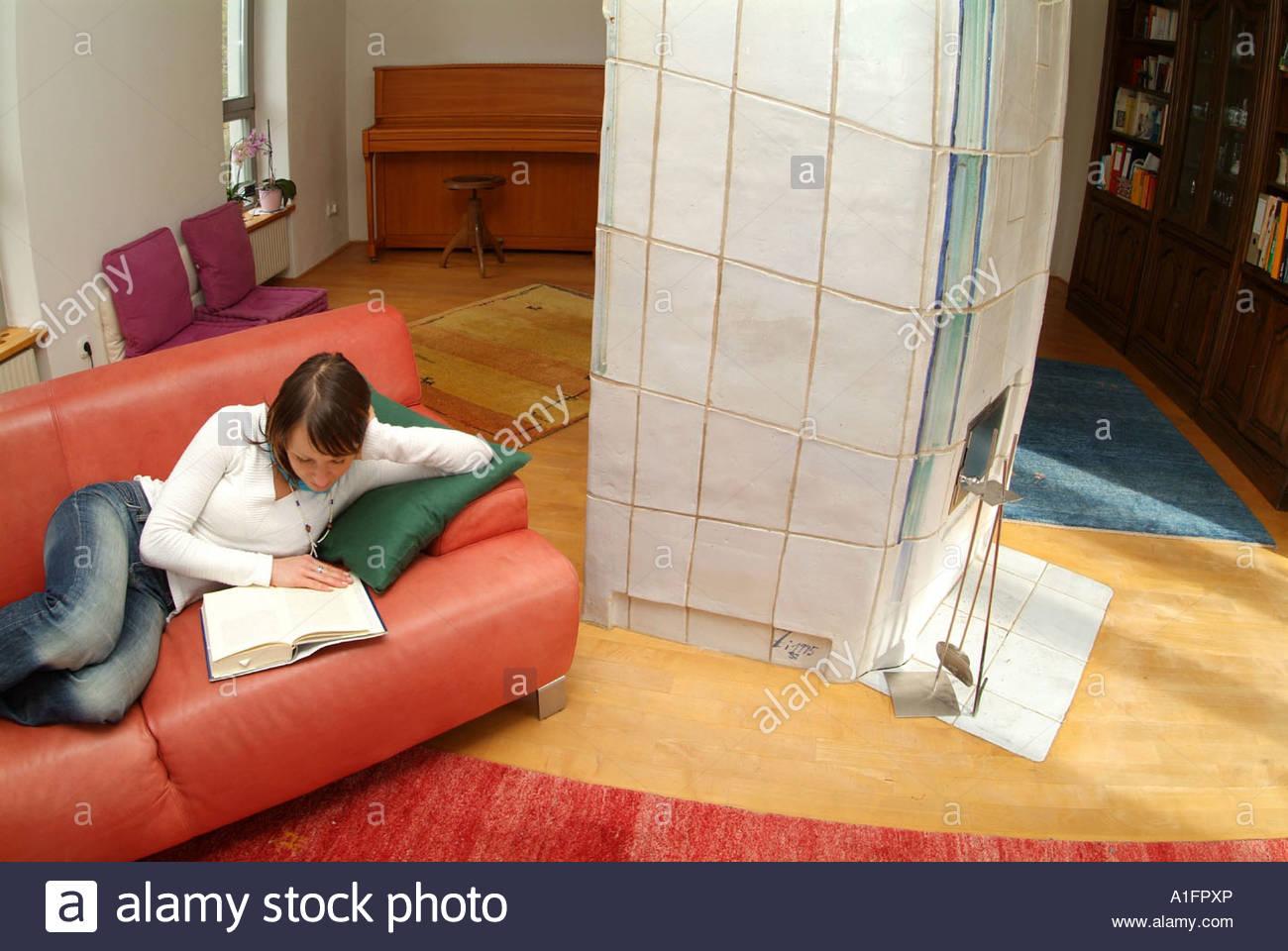 Junge Frau liegt gemütlich auf einer Couch im Wohnzimmer und liest ...