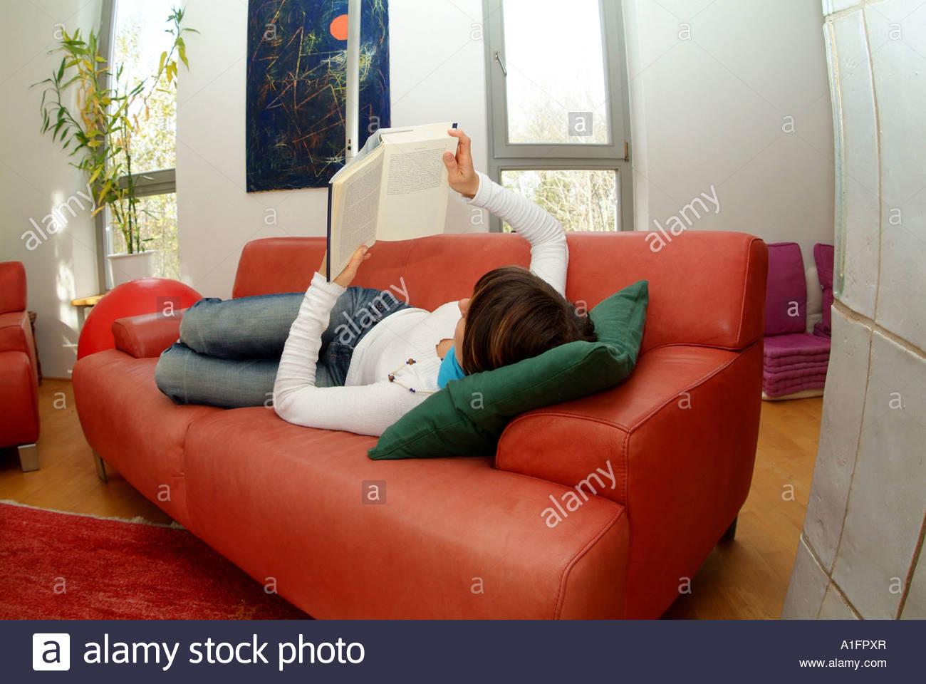 junge frau liegt gemütlich auf einer couch im wohnzimmer und liest
