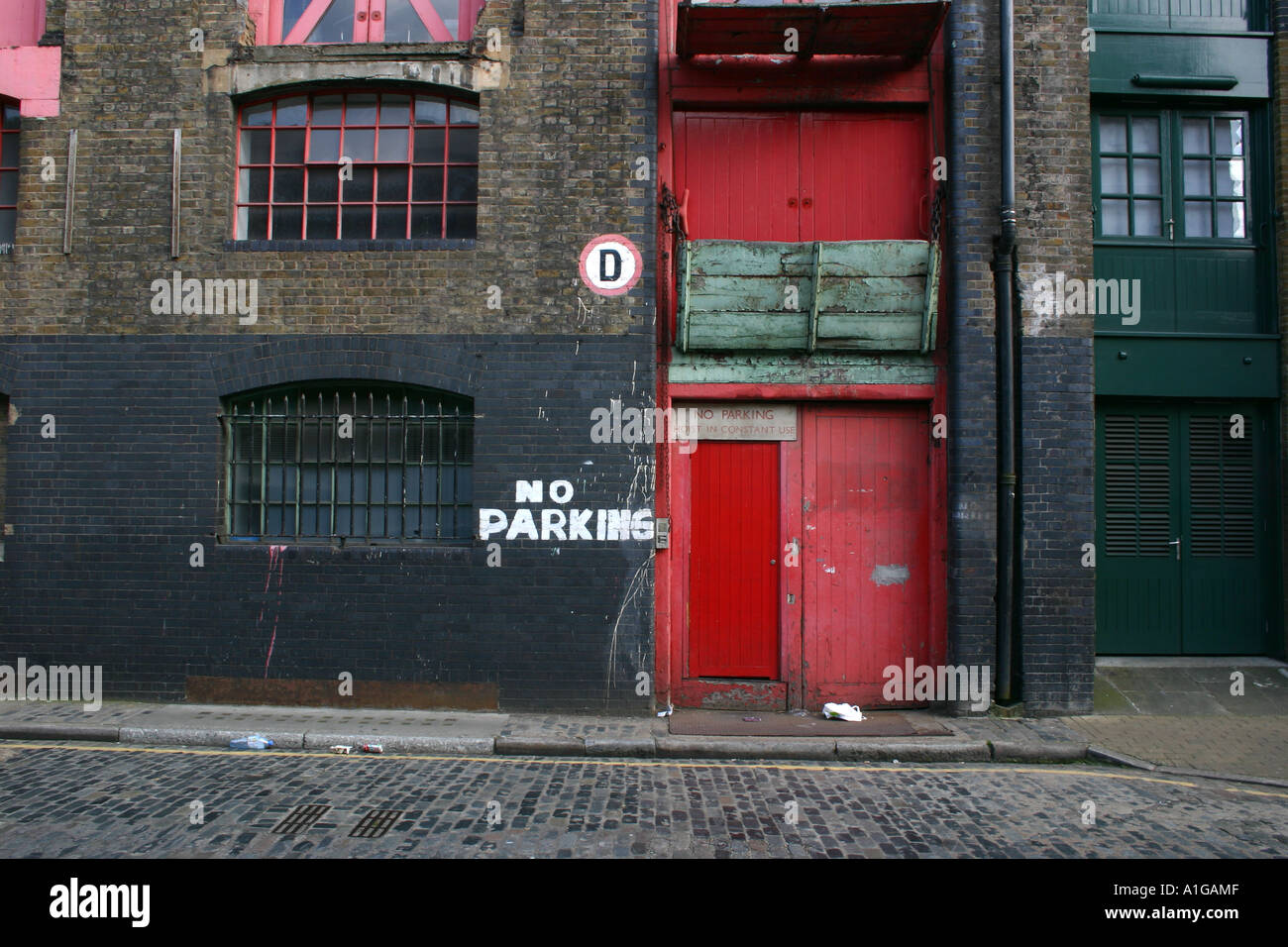 Old Brick Warehouse With Bright Red Doors In Wapping East London With No  Parking Sign Painted On Wall