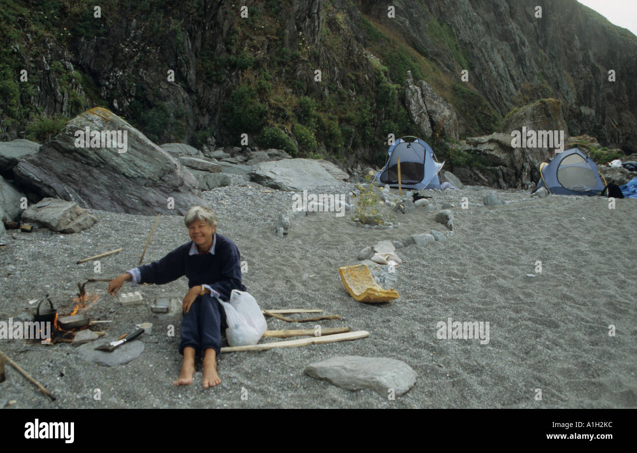 Woman c&er cooking on Cornish beach with Northface tadpole tents in background Cornwall UK & Woman camper cooking on Cornish beach with Northface tadpole tents ...