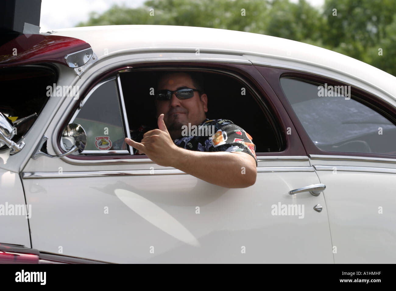man driving looking out of a classic old car window giving