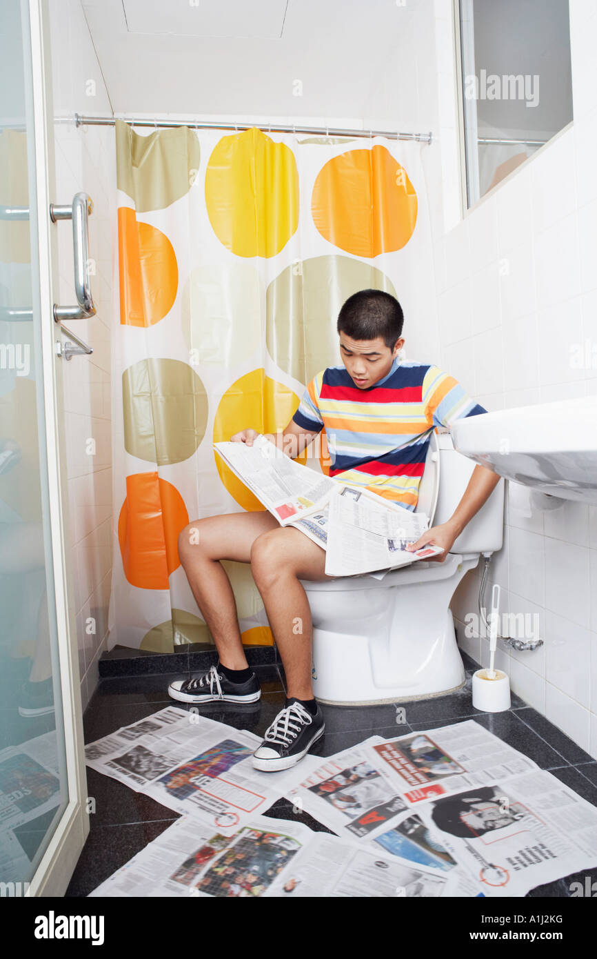 Young Man Sitting On A Toilet Bowl And Reading A Newspaper ...