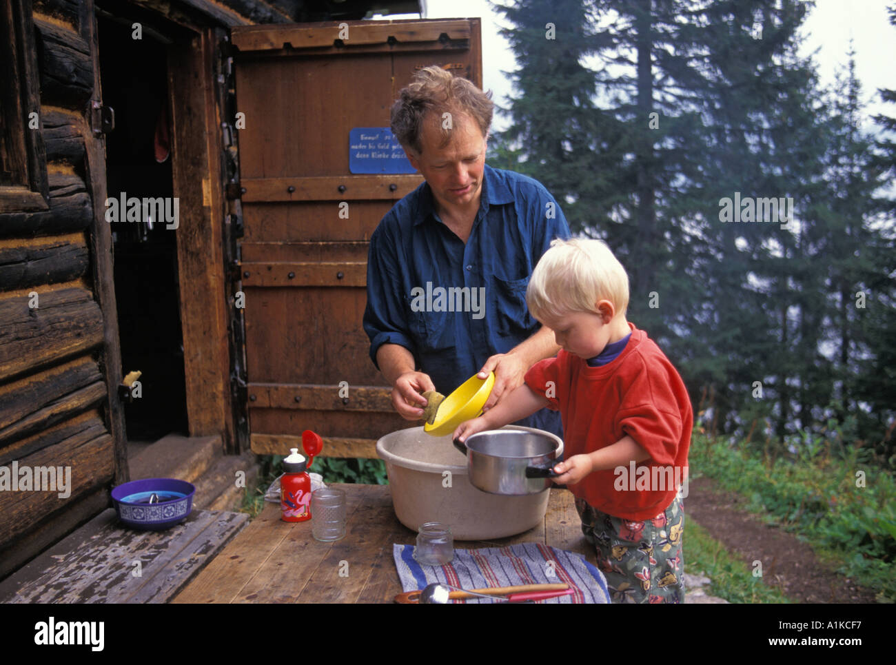 Father And Two Year Old Boy Washing The Dishes In Front Of A Log Cabin MR