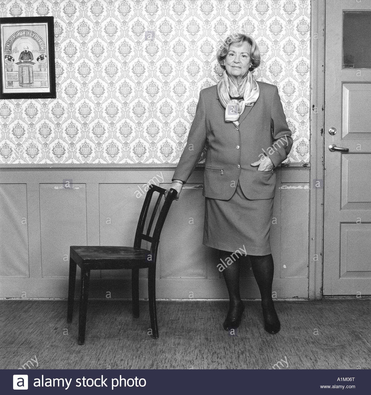 Mature woman wearing skirt jacket and high heels leaning to a chair wall  behind her - Mature Woman Wearing Skirt Jacket And High Heels Leaning To A