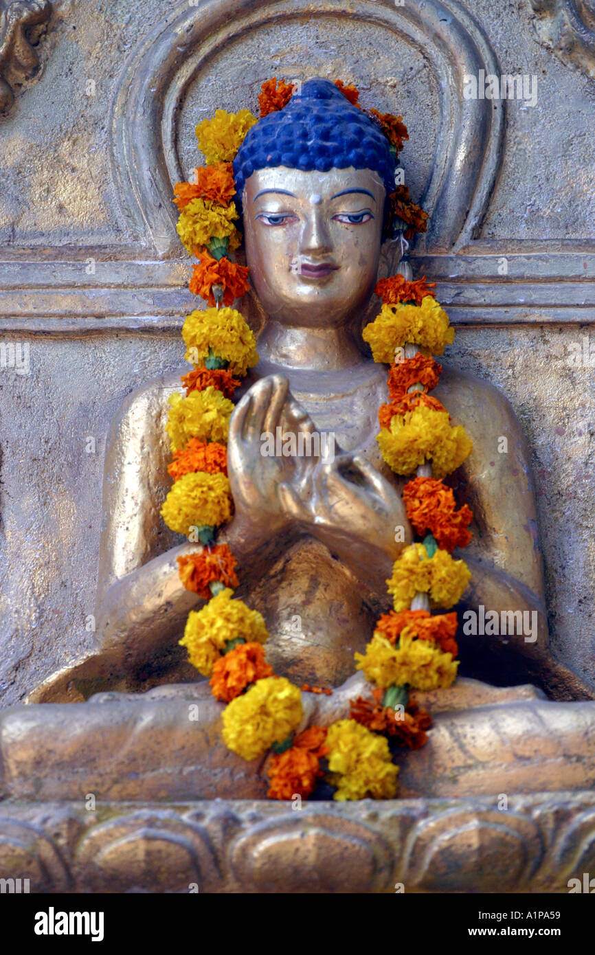 A Buddha Statue Is Decorated With A Flower Garland Near