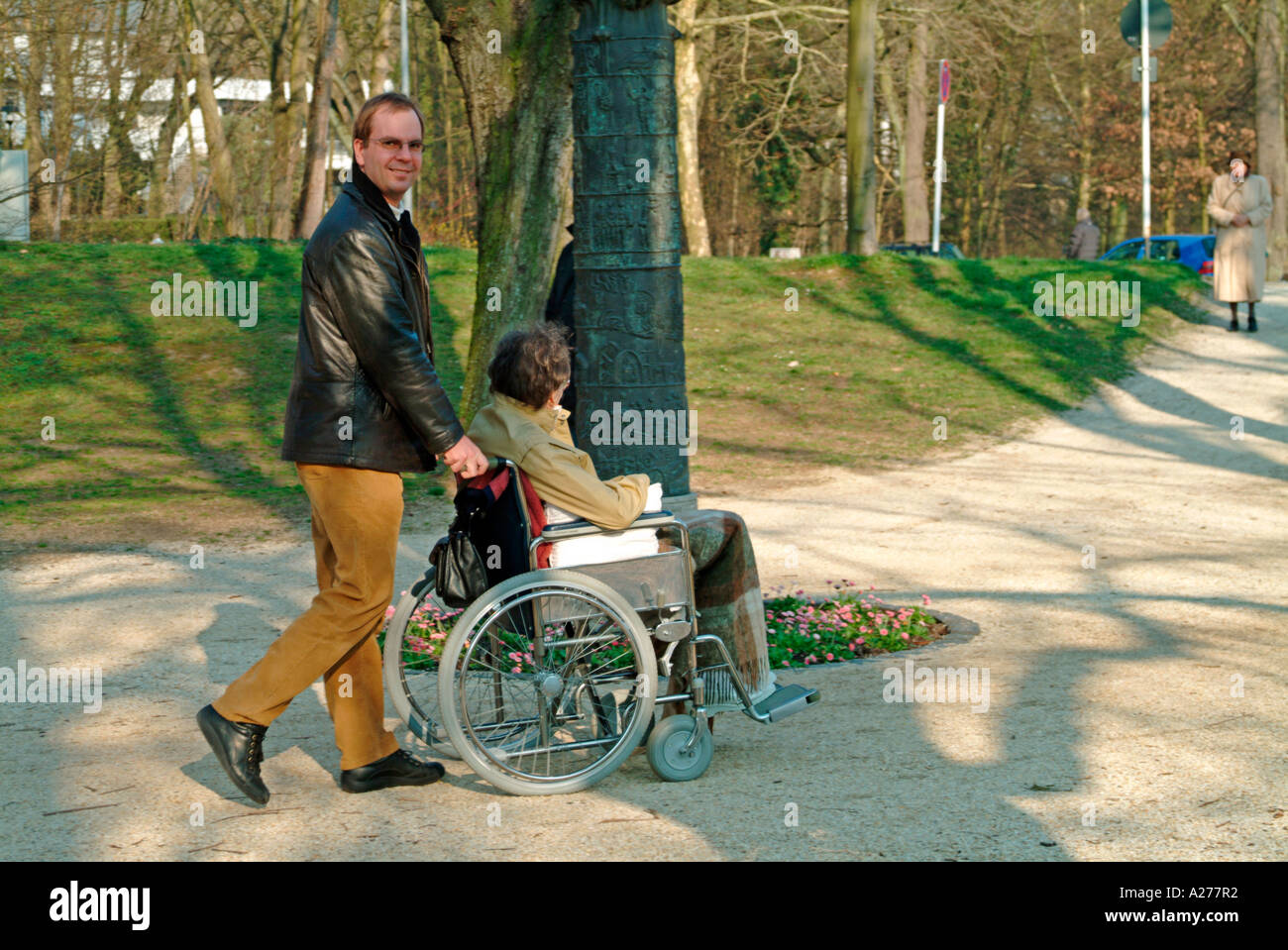 Young Man Pushing A Wheel Chair Wheelchair With An Old
