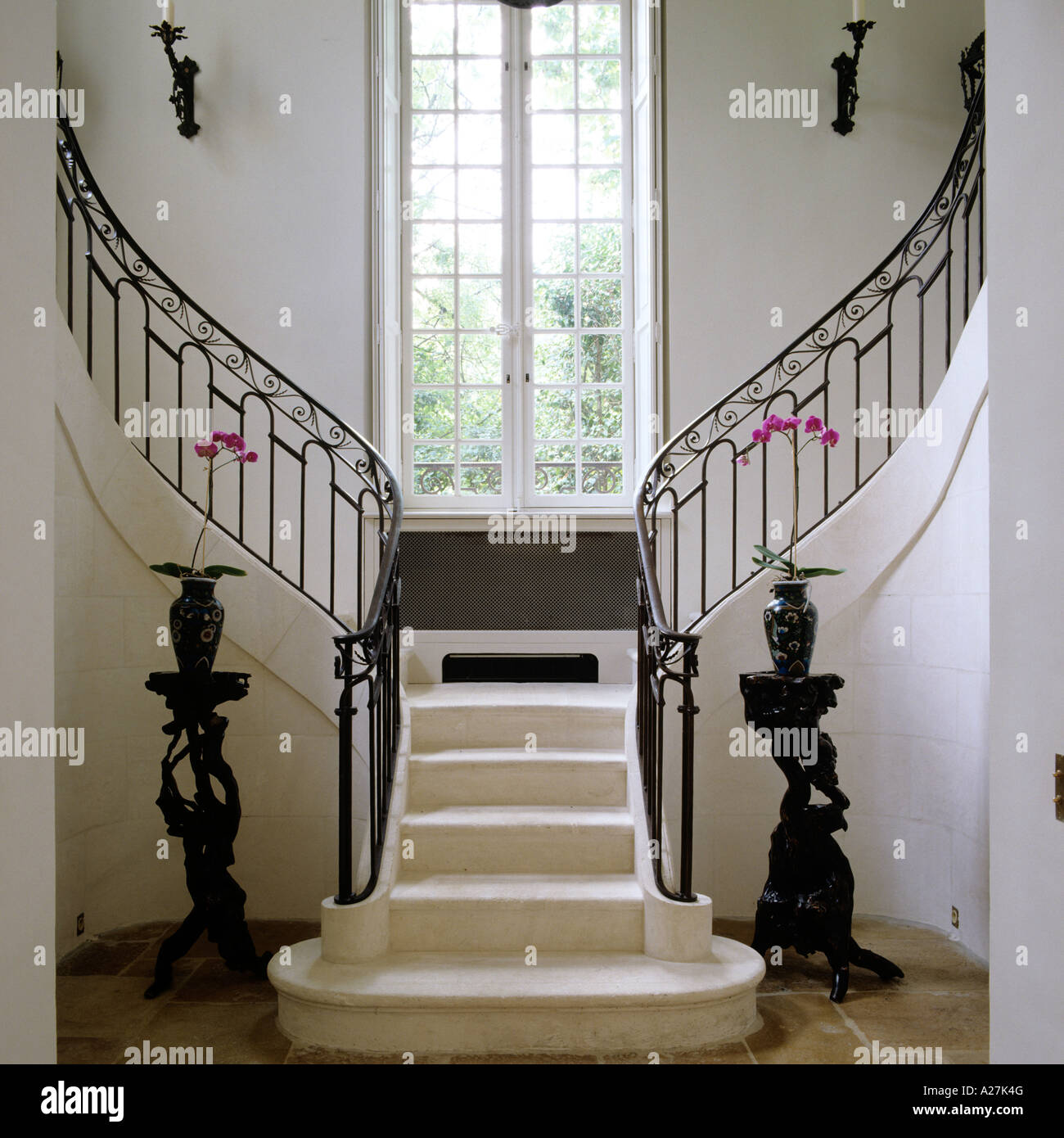 stock photo stone grand staircase with wrought iron banister and large paned window