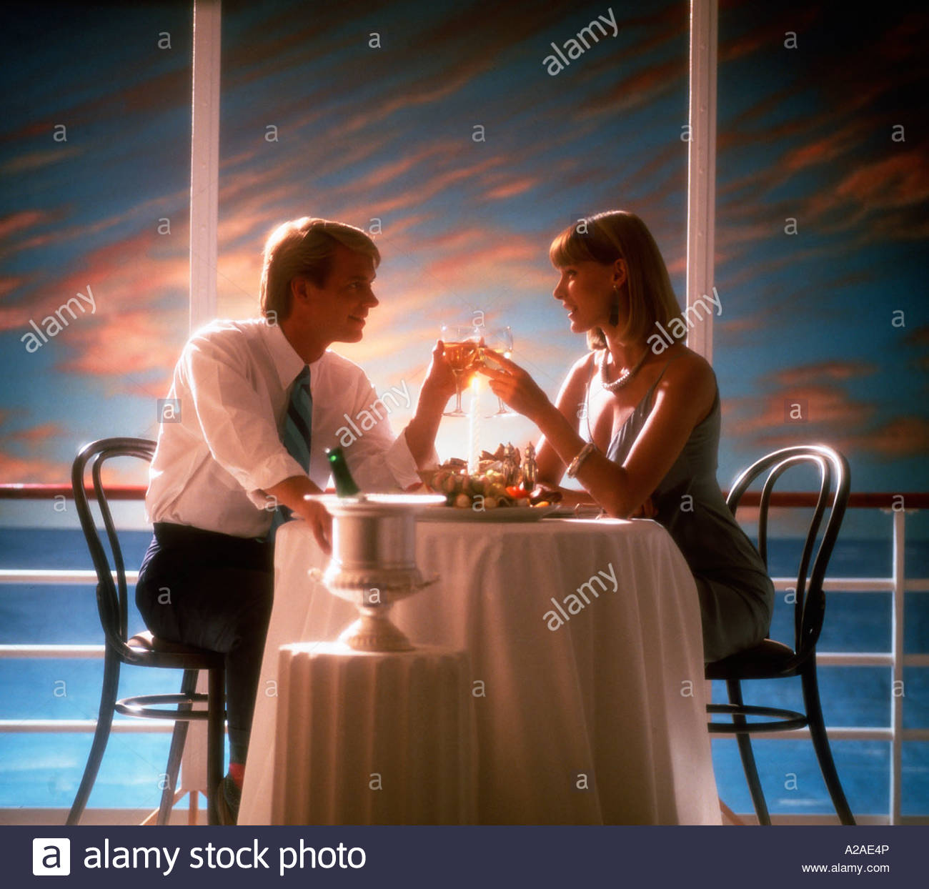 Romantic dinner for two on board a cruise ship, sun setting in the ...