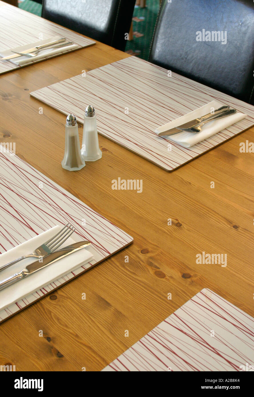Modern restaurant table setting - Modern Wooden Restaurant Table Showing Knives Forks And Condiment Set With Place Settings And Mats