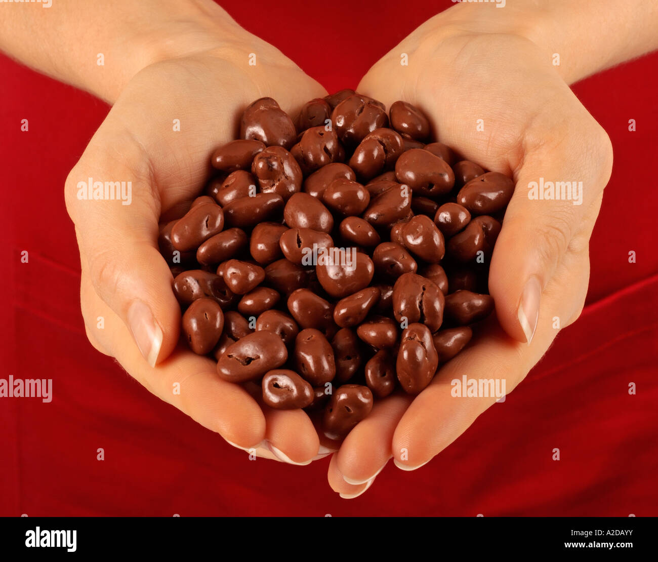 WOMAN WITH HANDFUL OF CHOCOLATE COVERED RAISINS Stock Photo ...