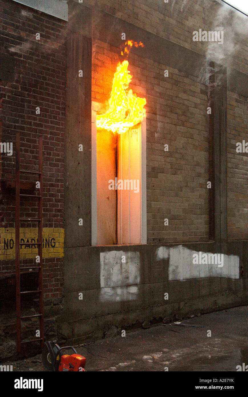 Flames In A Doorway Of A Brick Commercial Warehouse Filled With - Furniture nearby