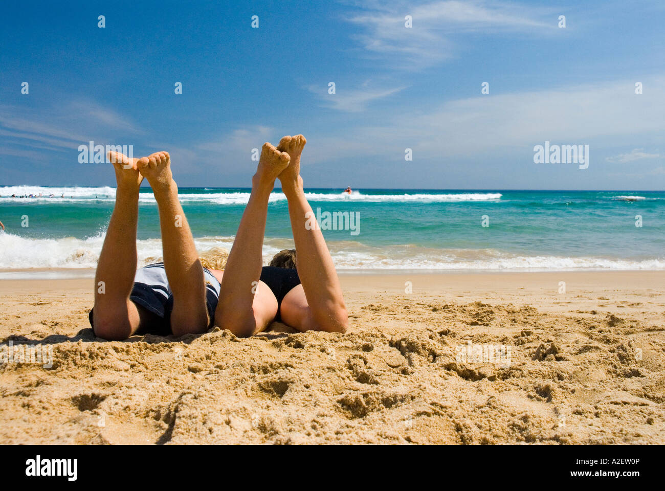Two People A Couple Lying On Tropical Beach Facing The Ocean Sand Blue Sky