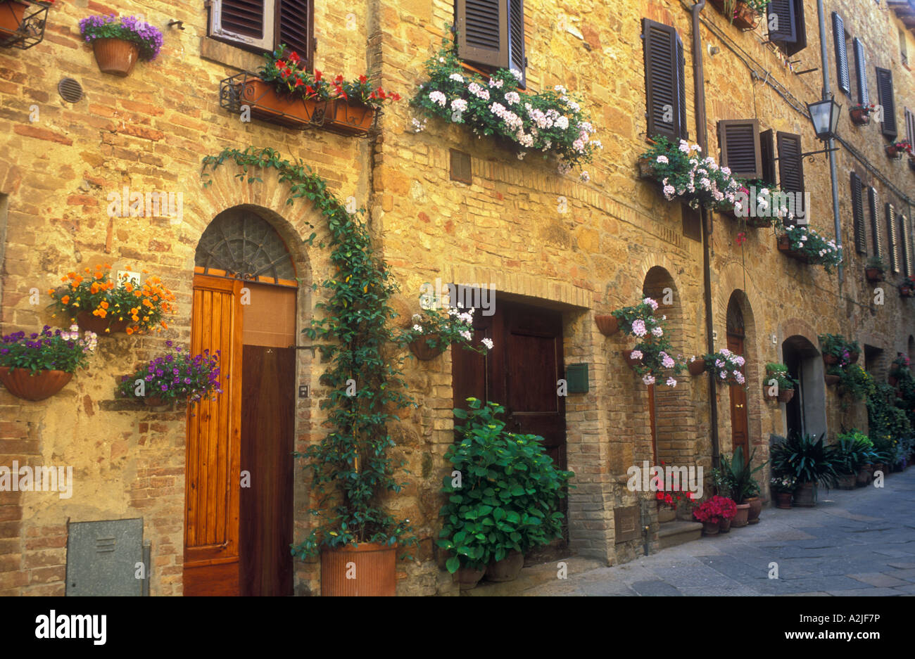 Italy Pienza Tuscany hanging flower baskets along a brick wall with doorways & Italy Pienza Tuscany hanging flower baskets along a brick wall with ...