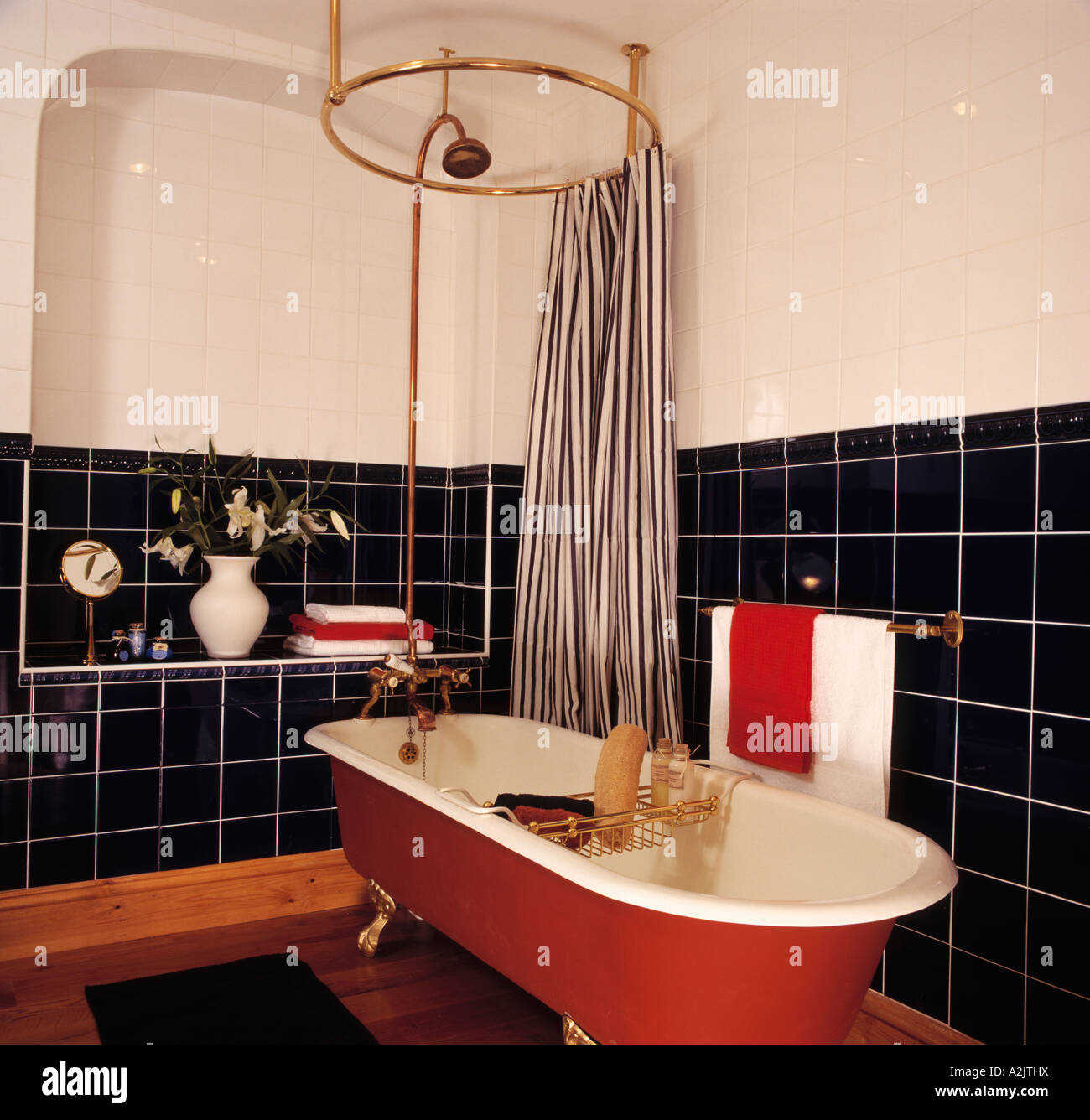 striped shower curtain on circular rail above red freestanding stock photo striped shower curtain on circular rail above red freestanding bath in black and white bathroom