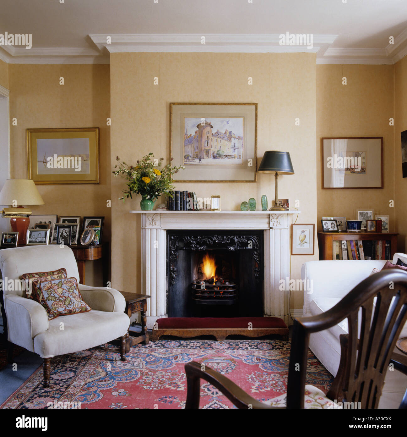 English country style living room with mantel piece, arm chair and ...