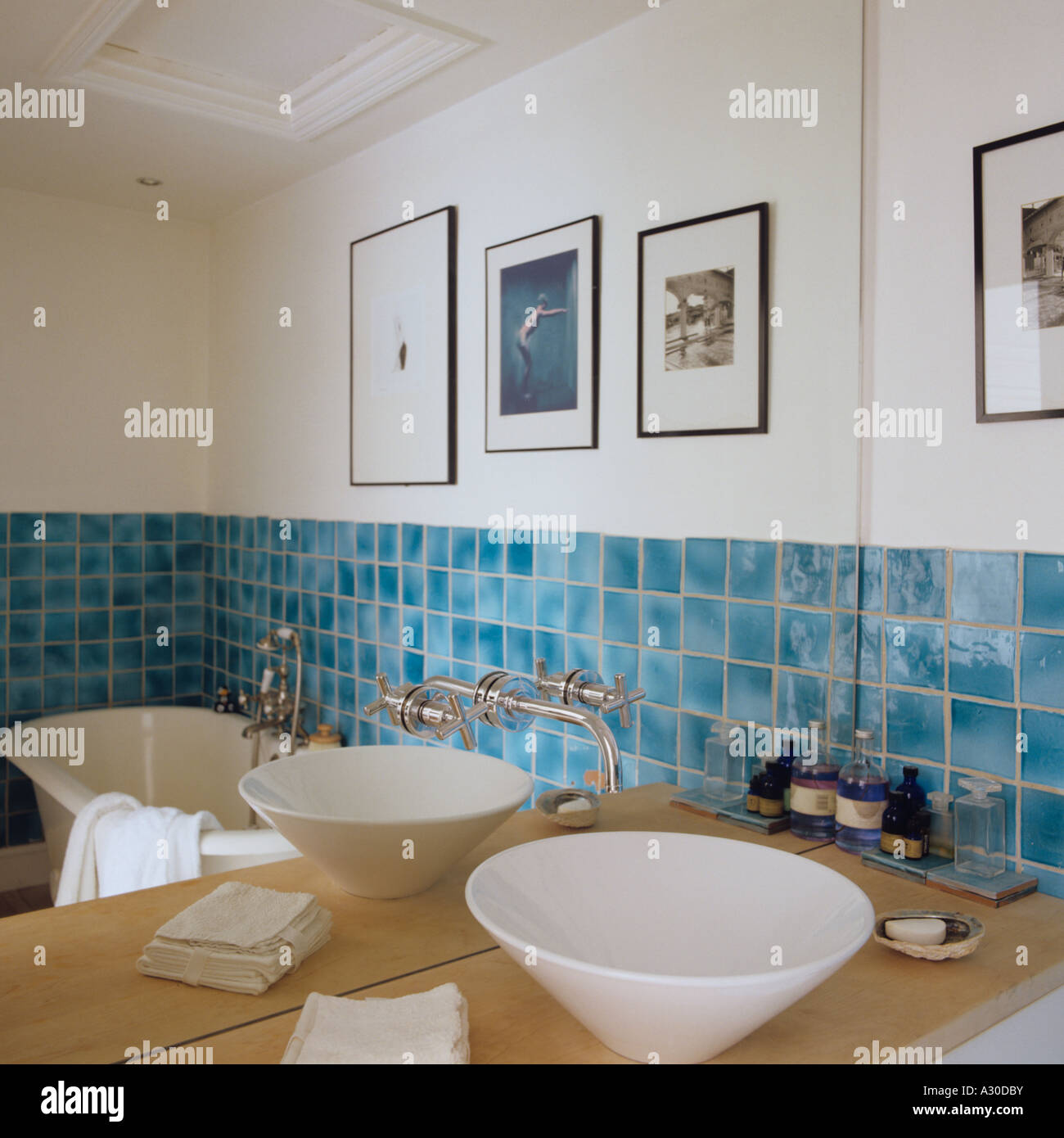 Contemporary wash basin in front of mirror in bathroom with turquoise tiles. Contemporary wash basin in front of mirror in bathroom with