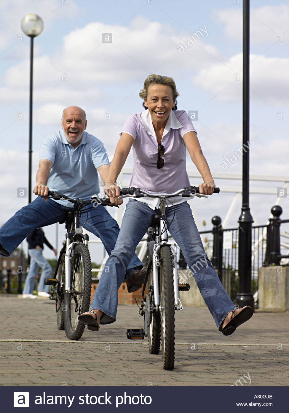mature couple riding bicycles stock photo, royalty free image