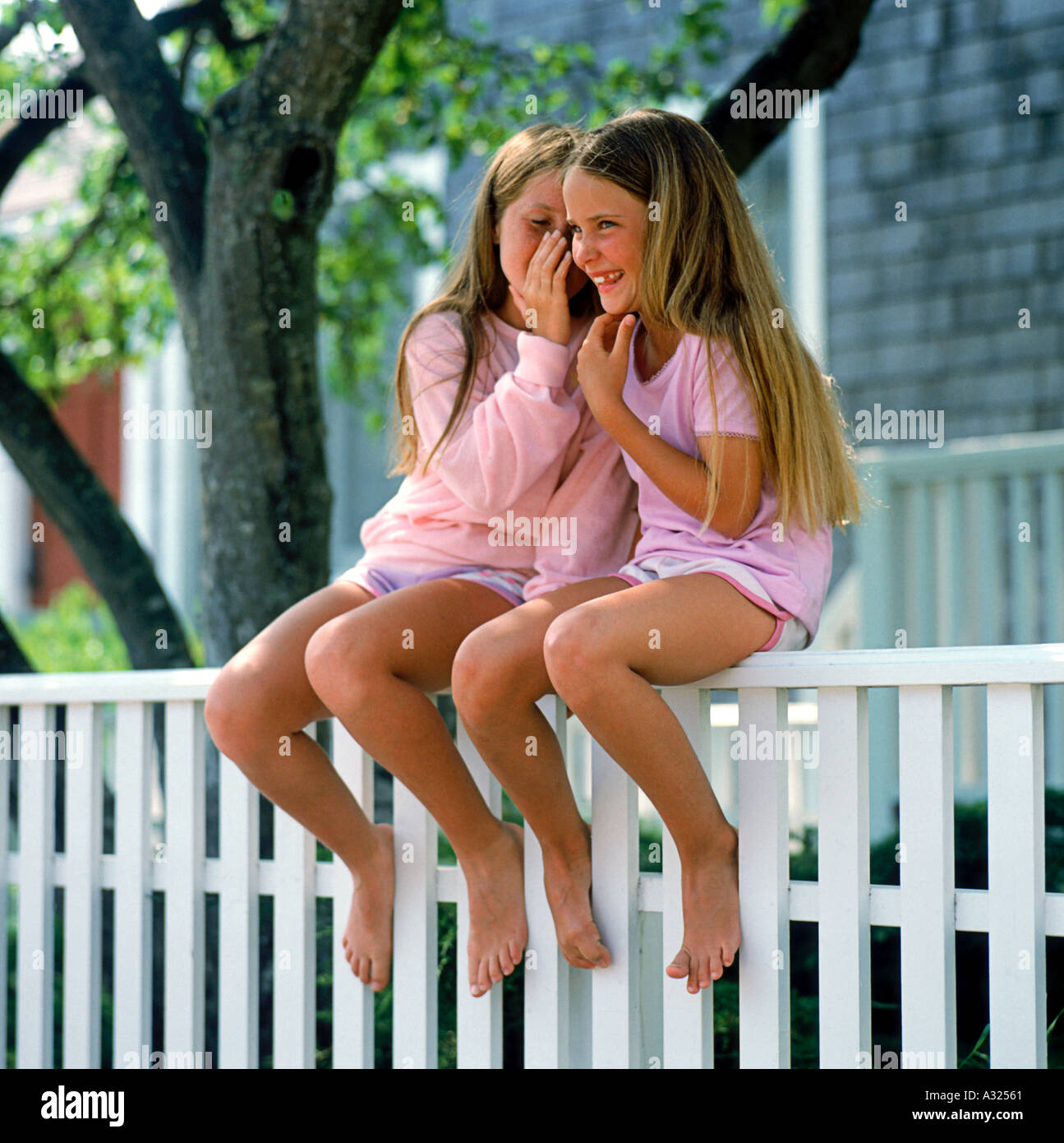 Young girls  Stock Photo - Two young girls with long hair sitting barefoot on a white  fence telling secrets and laughing together