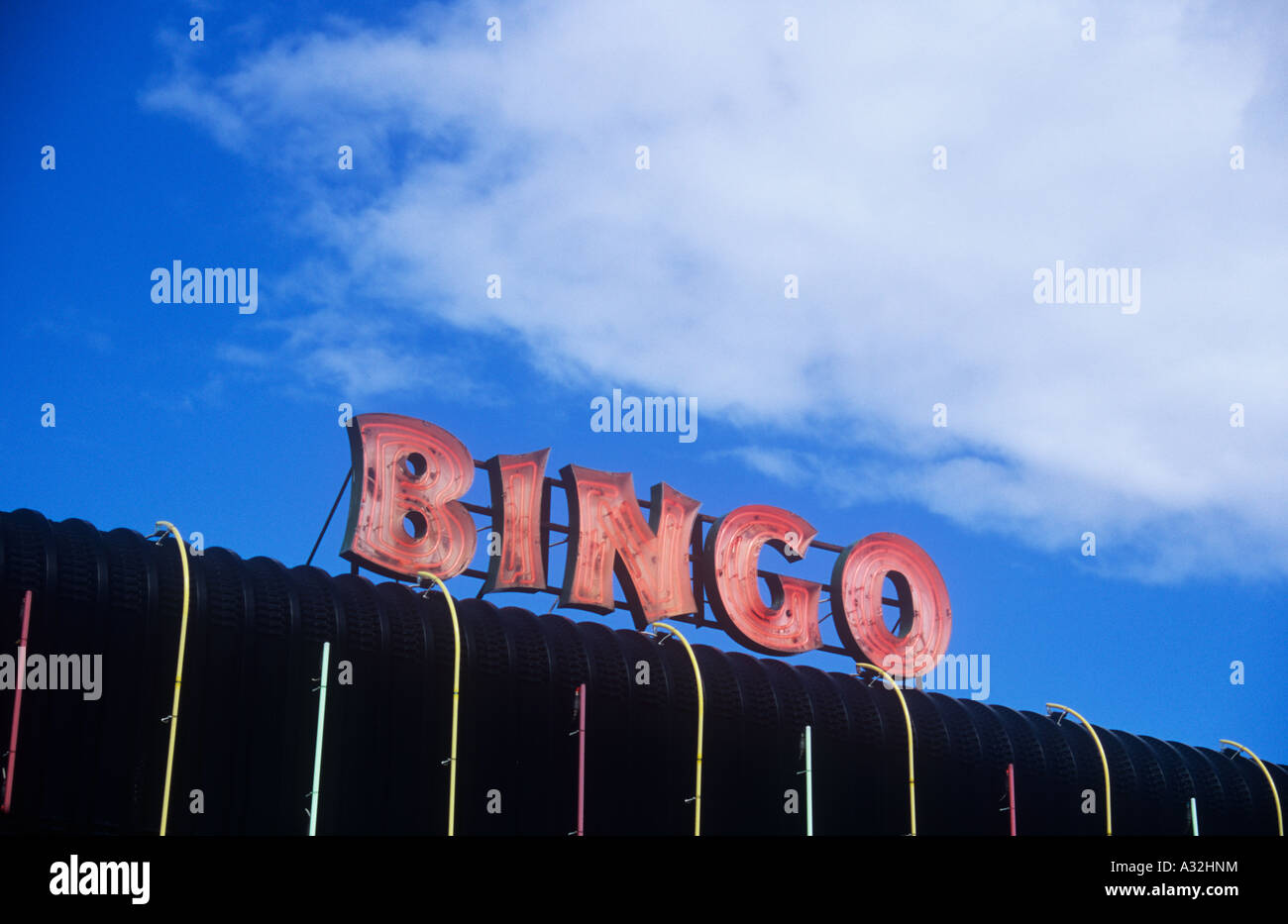 Red neon sign stating bingo on black plastic roof with coloured red neon sign stating bingo on black plastic roof with coloured strip lights under blue sky with large white cumulus cloud mozeypictures Images