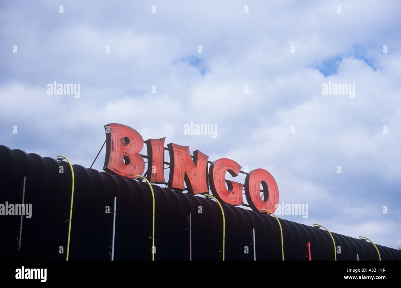 Red neon sign stating bingo on black plastic roof with coloured red neon sign stating bingo on black plastic roof with coloured strip lights under almost completely cloudy sky mozeypictures Images