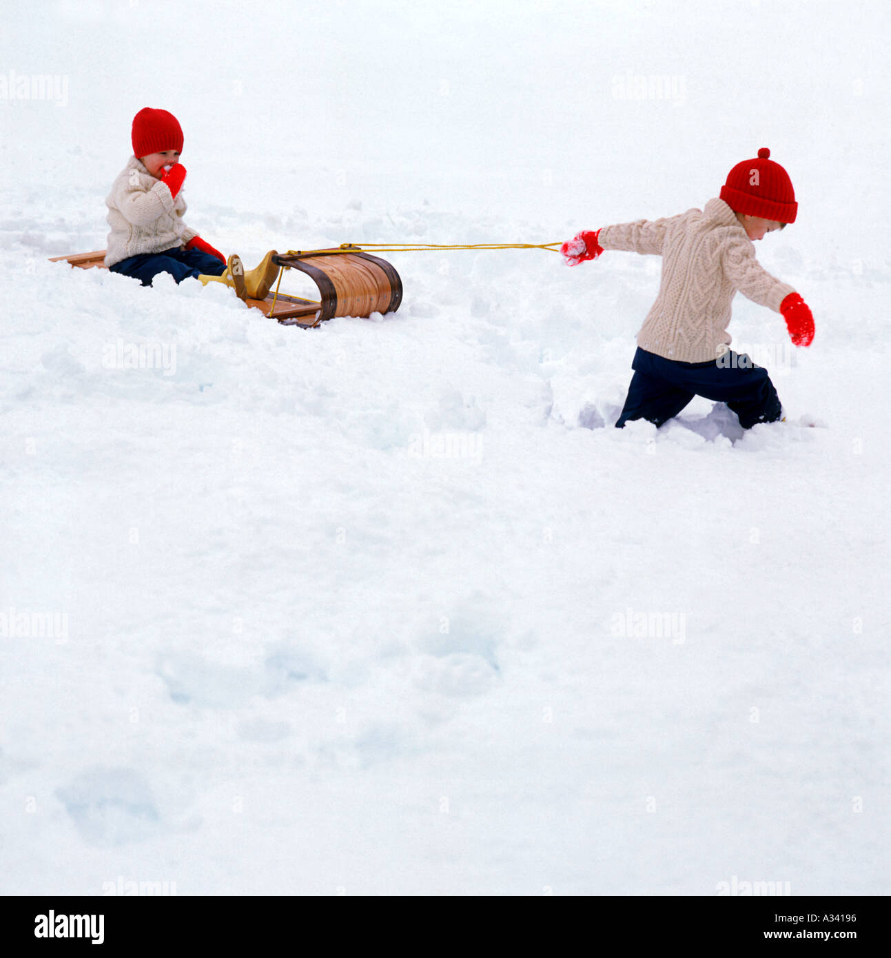 a young child pulling another child on a toboggan type sled