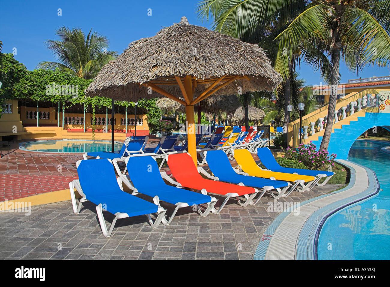 Several colourful sun beds and umbrella on a poolside patio near Trinidad Sancti Spiritus Province Cuba & Several colourful sun beds and umbrella on a poolside patio near ...
