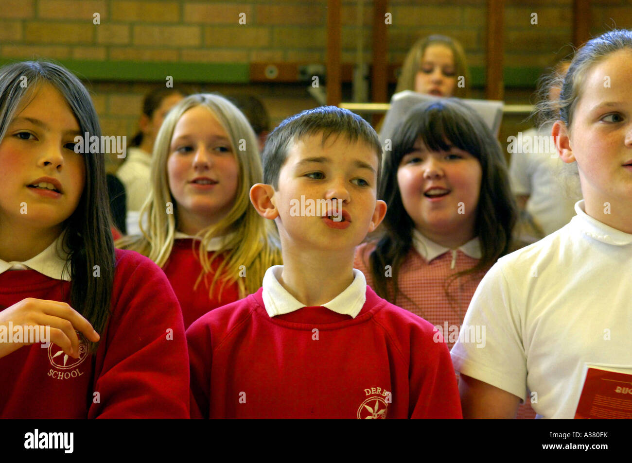 pre teens Stock Photo - school assembly children pupils students pre teens primary  british colour color education learning girls boys red sing singing