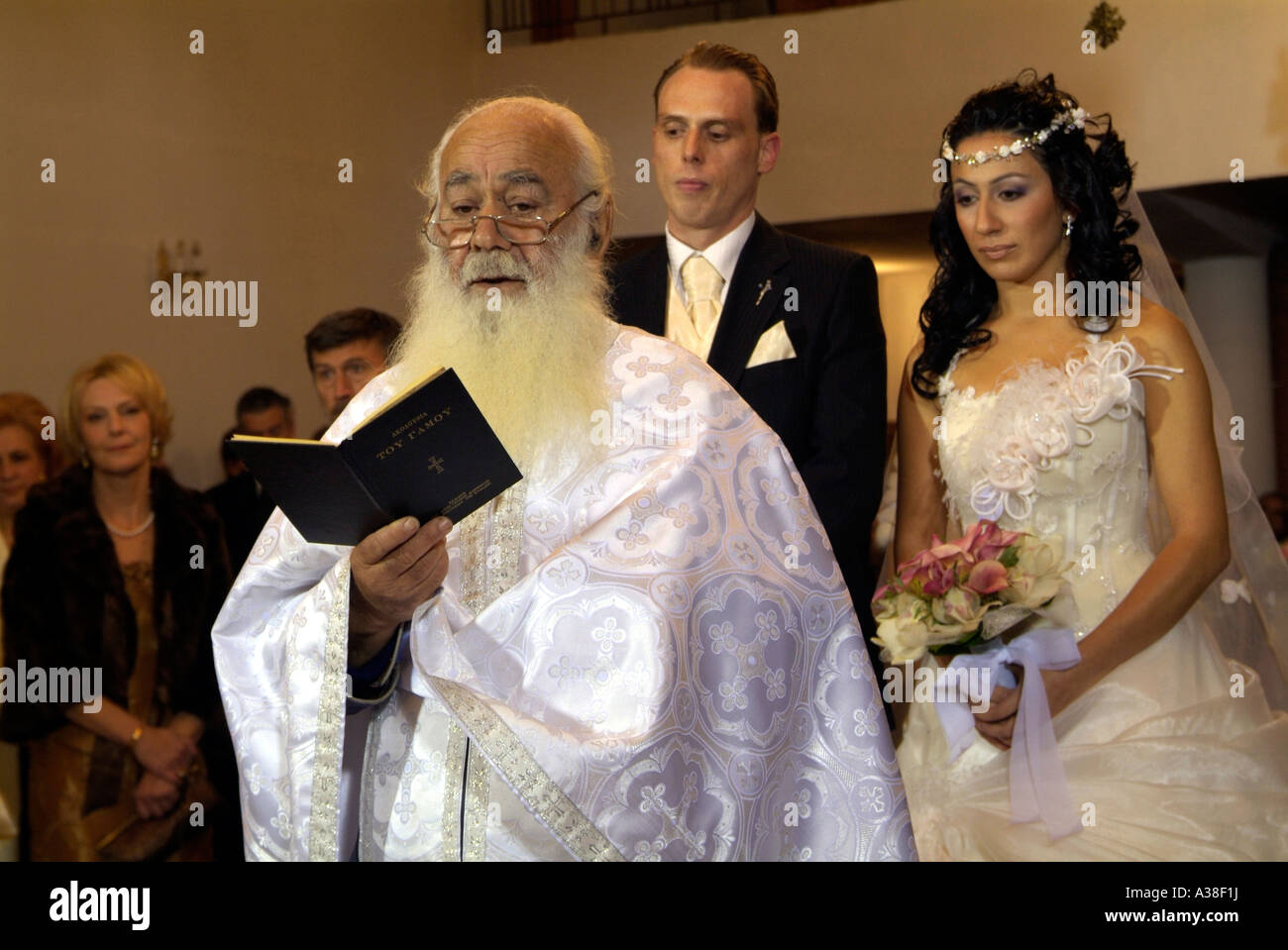 The Priest Reading From Bible During A Greek Orthodox Wedding Ceremony