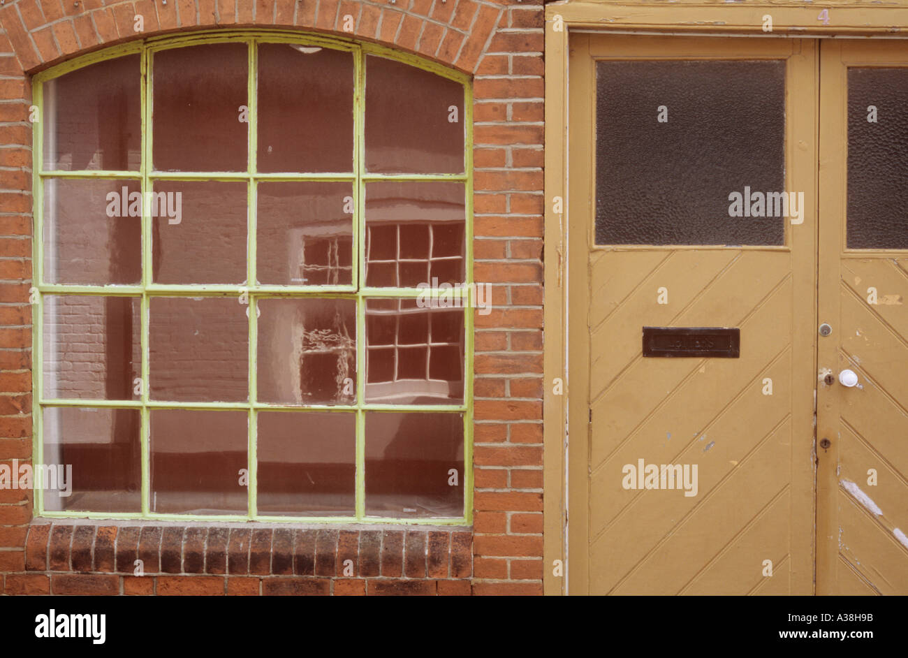 Arched Metal Framed Window Set In Red Brick Typical Of A Victorian Warehouse  And Adjacent Door