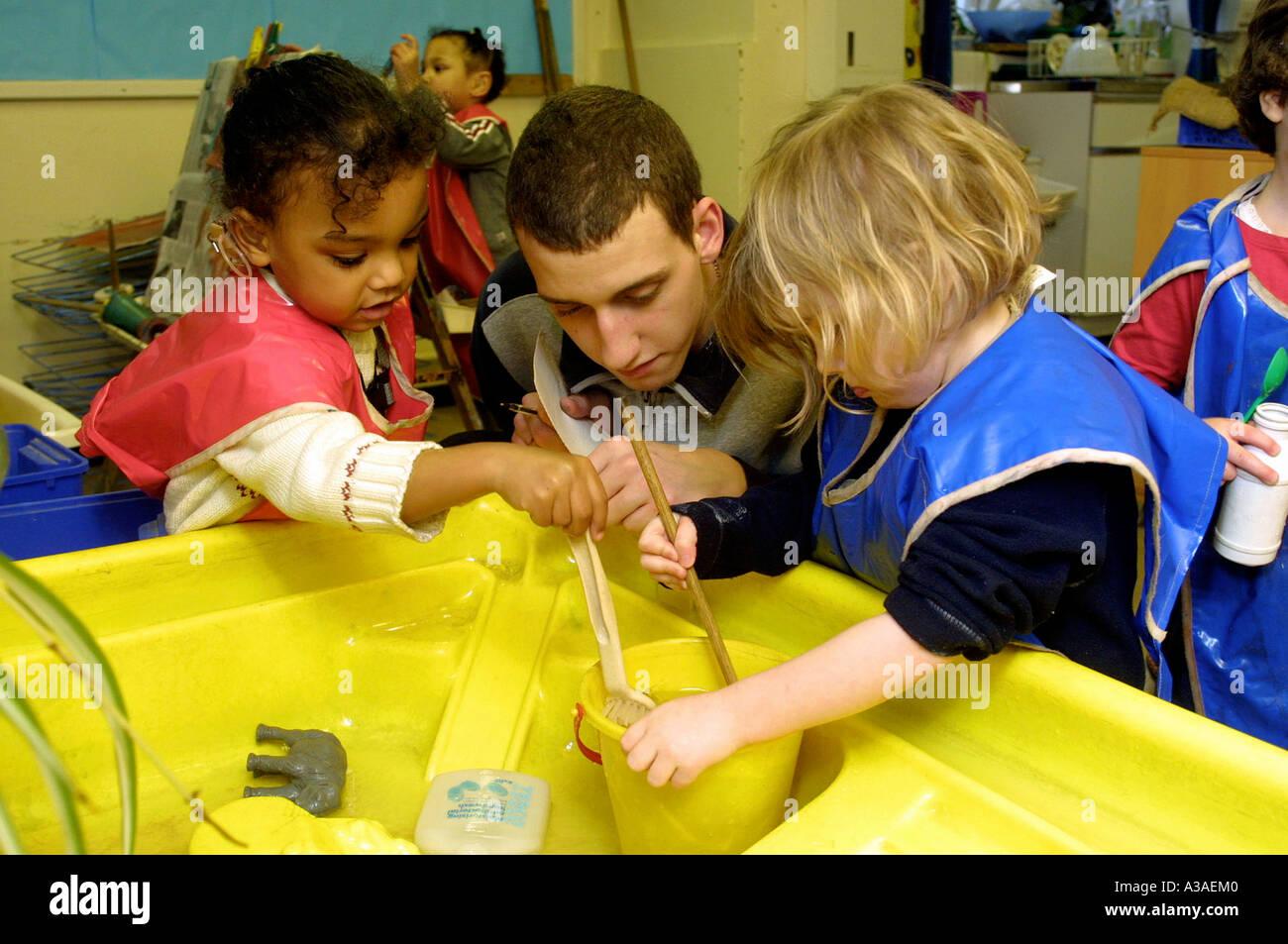 Male nursery school teacher playing with children in classroom ...