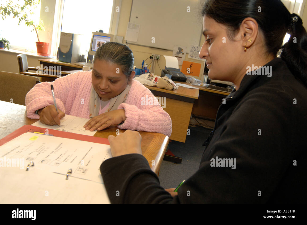 A woman with learning disabilities fill in a form with her carer ...