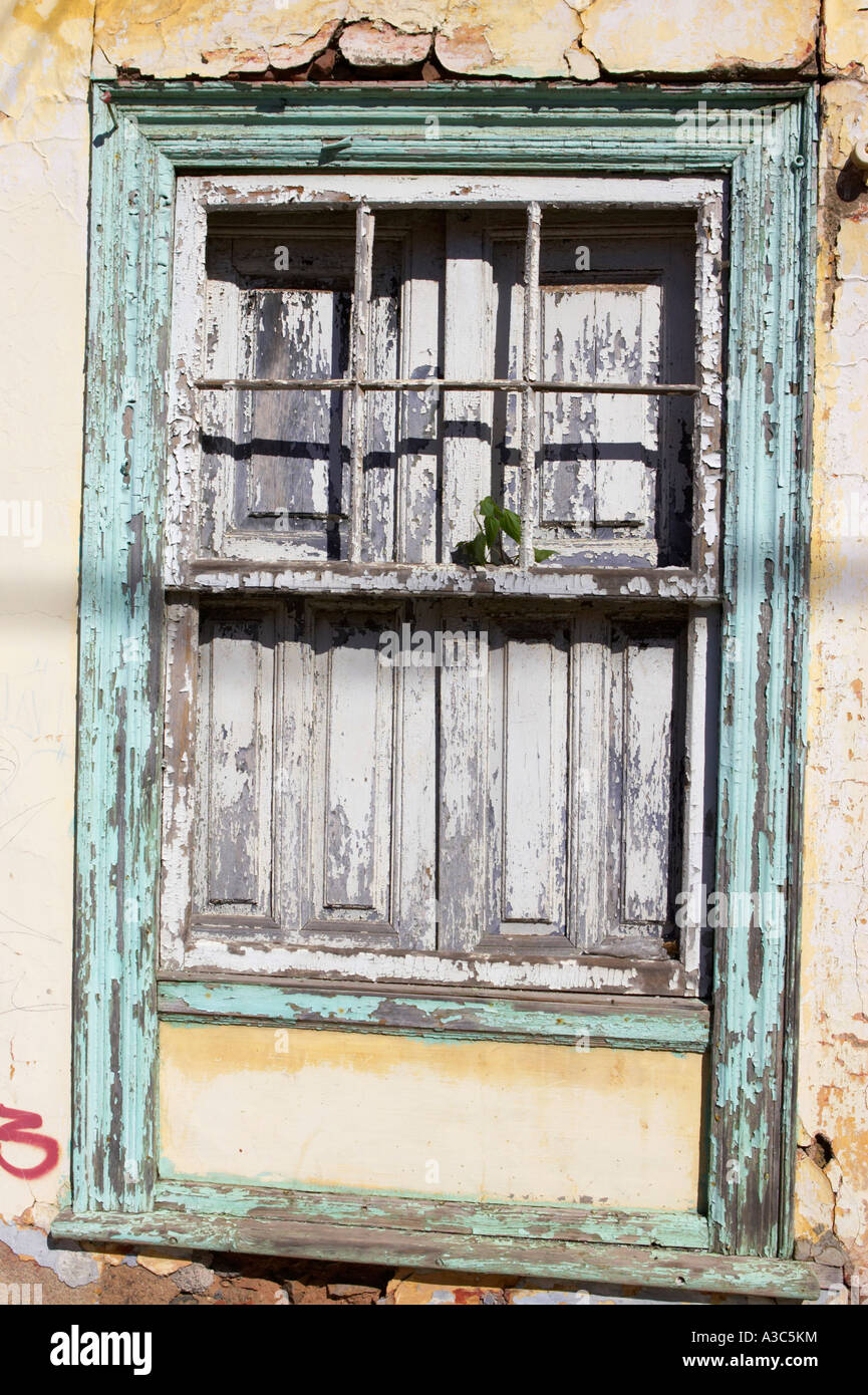 Old wooden window with green painted frame set in old red brick