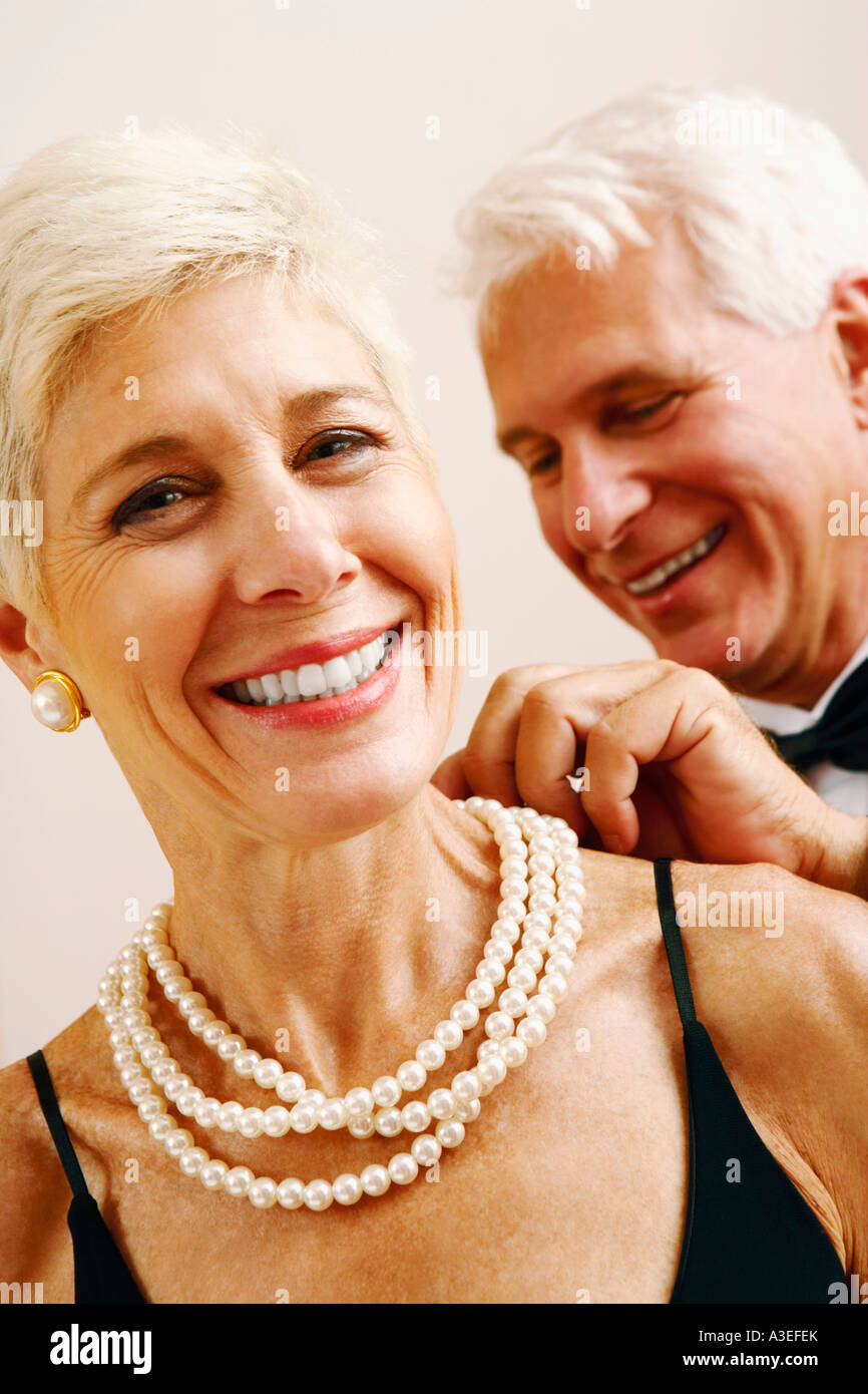 Closeup Of A Mature Man Putting A Pearl Necklace Around A Senior Woman's  Neck
