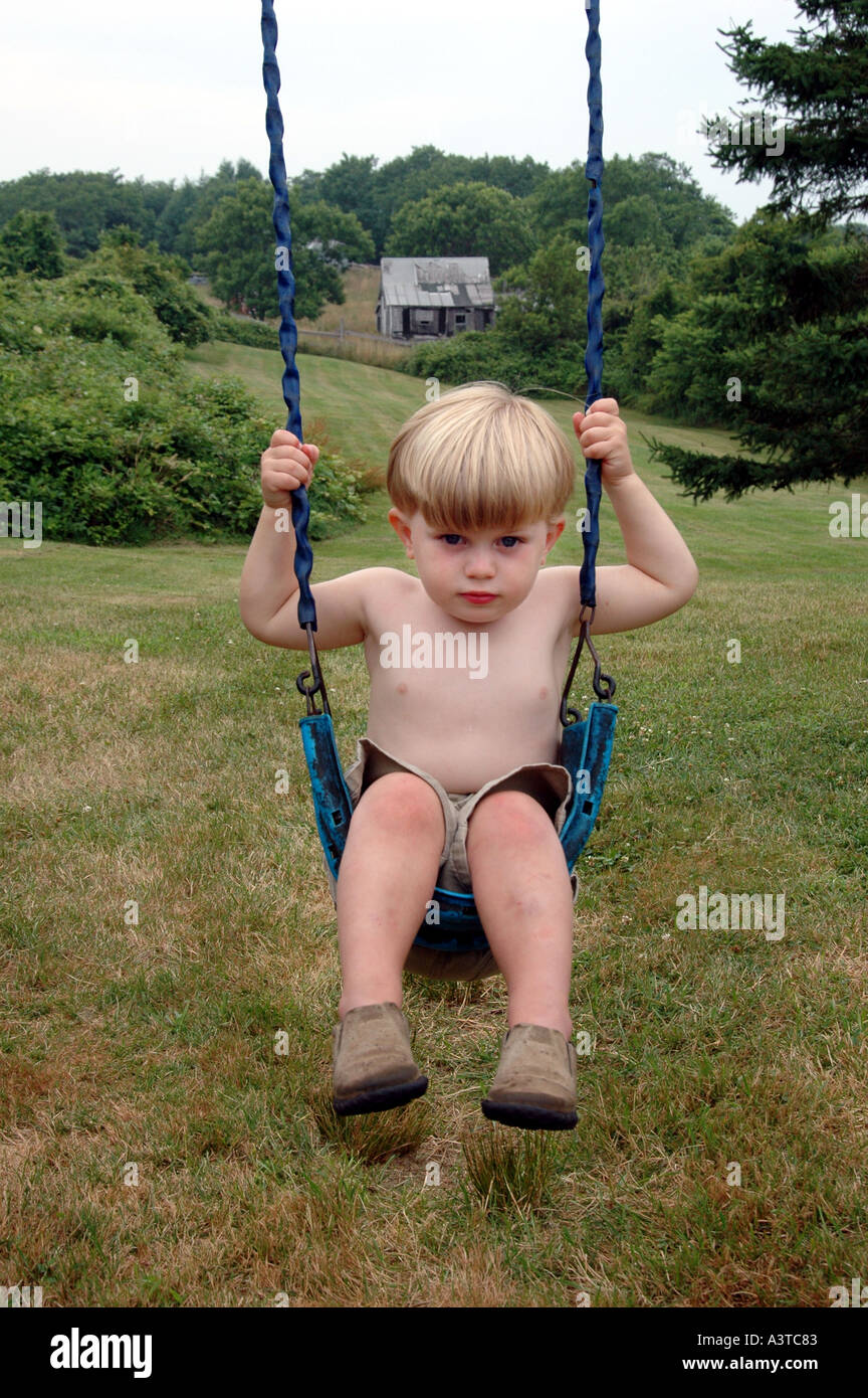 youth child young baby boy playing on swings swing in backyard