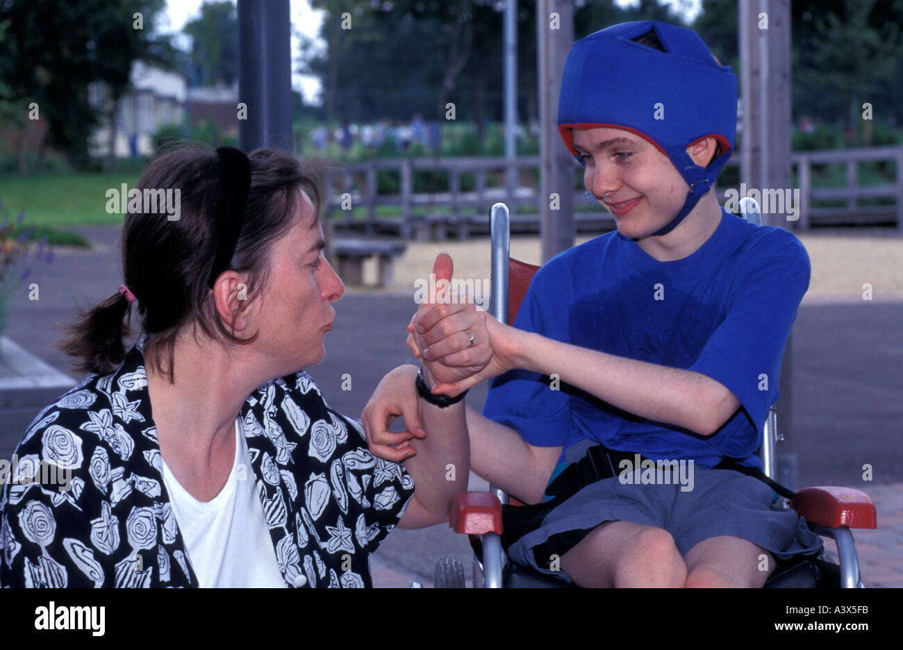 autistic-boy-in-wheelchair-with-carer-at