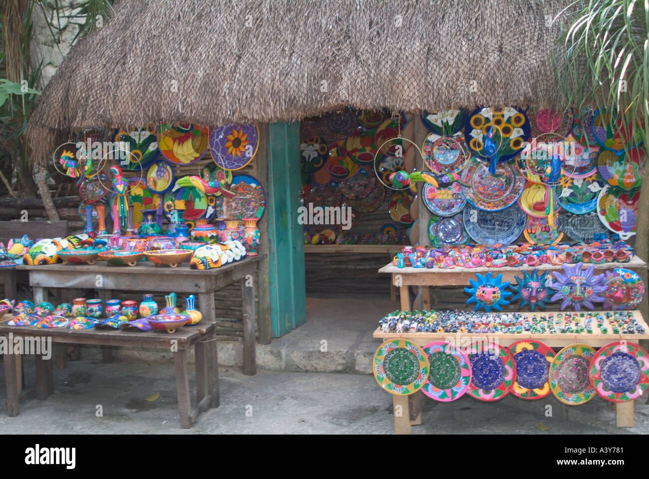 front of mayan wooden hut displaying colour in artwork and pottery xcaret park riviera maya mexico