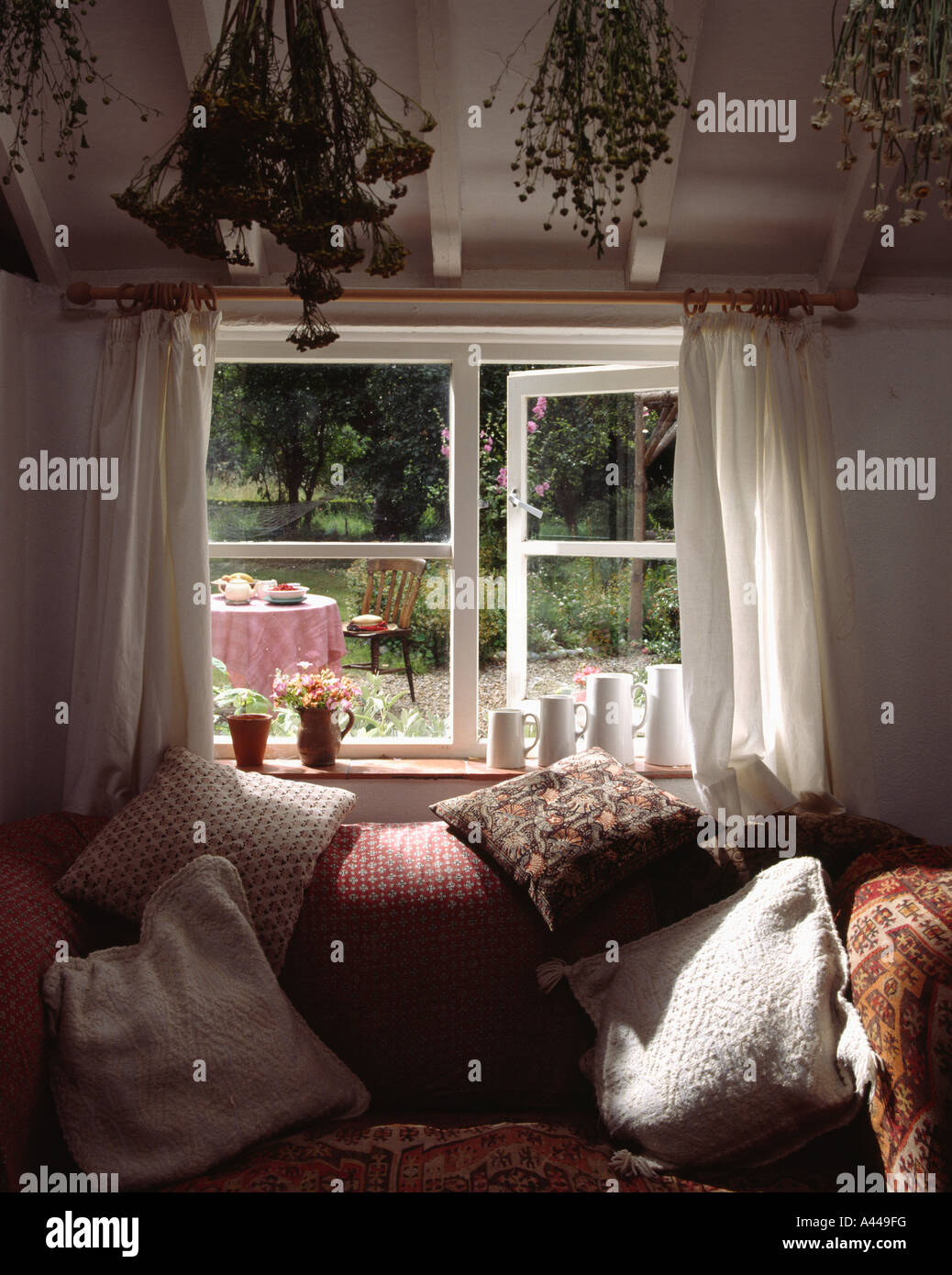 cottage livingroom with comfy sofa below open window with view of