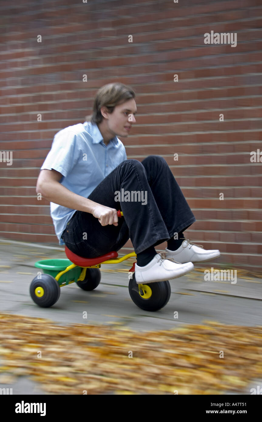 stock photo young man riding small childrens toy tricycle or bike - Small Childrens Images