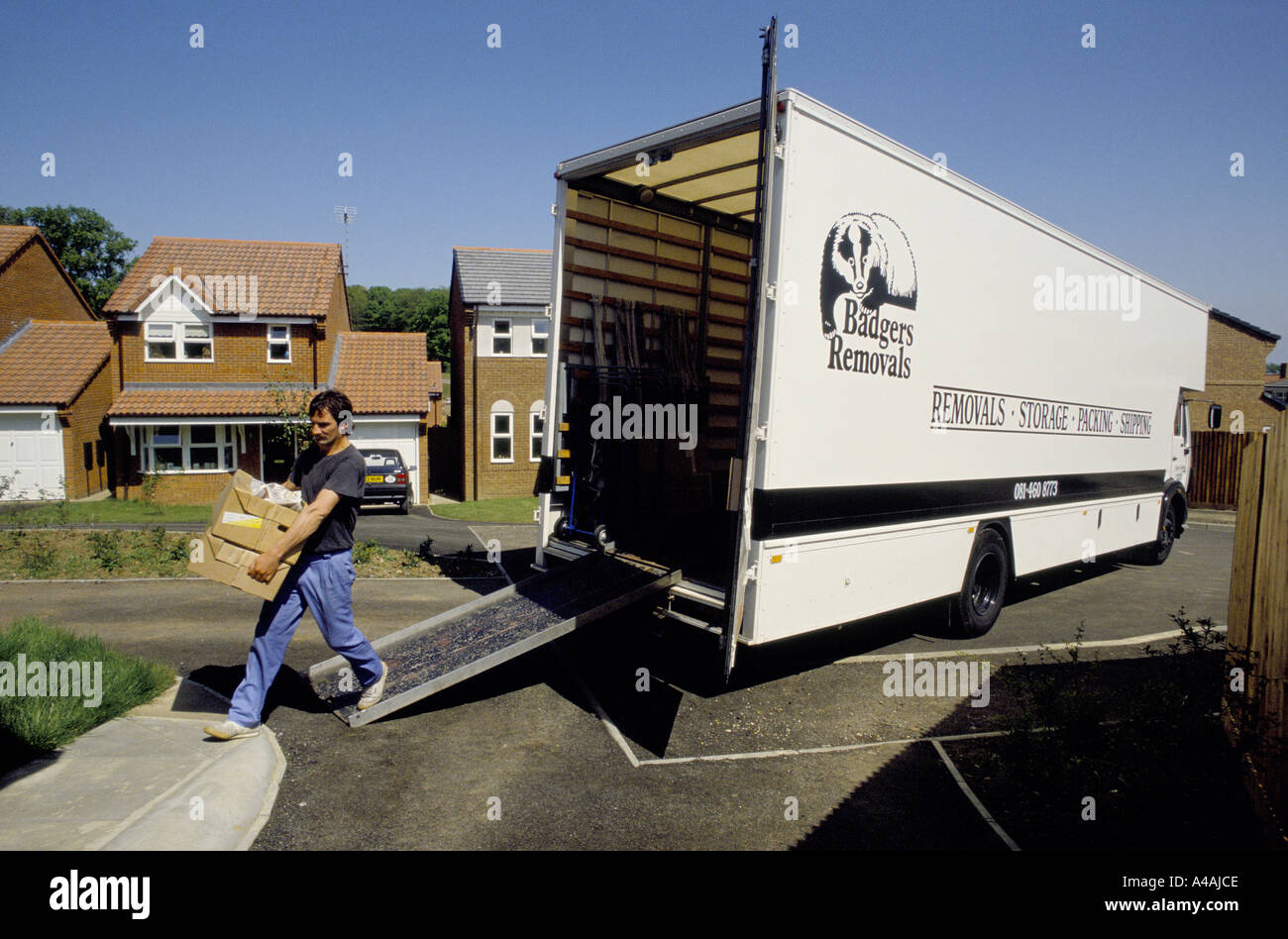 Man carrying boxes off a truck lorry moving into a new for Moving to new house