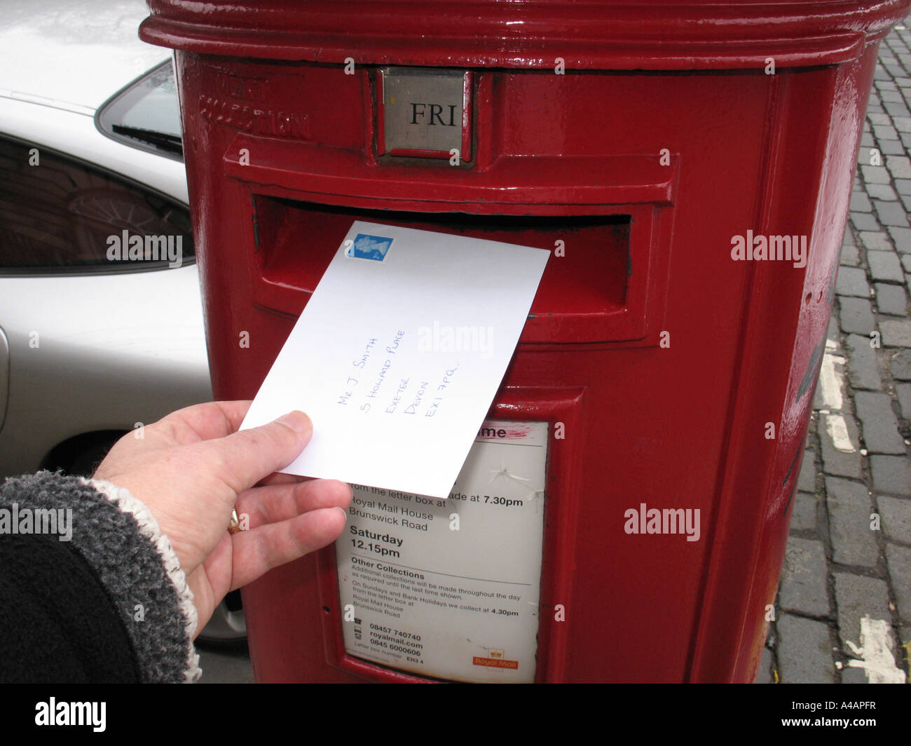 Posting A Letter In A Royal Mail Post Box Uk Stock Photo