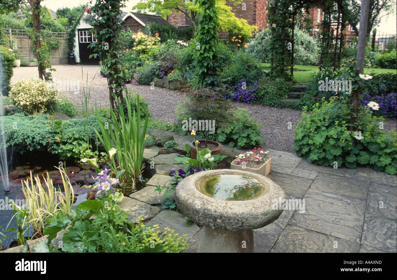 Bird bath and pond in wildlife friendly garden stock photo for Pond friendly plants