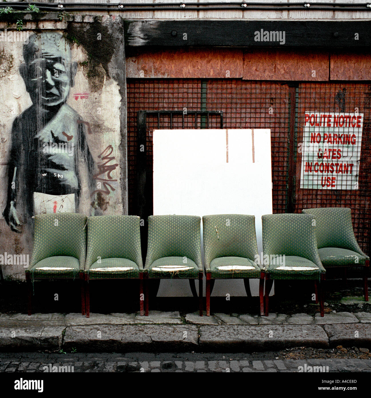 Stock Photo   Used Furniture Dealers Street Display Off Brick Lane In  Londons East End With Wall Graffiti Mural Stencil Possibly By Banksy