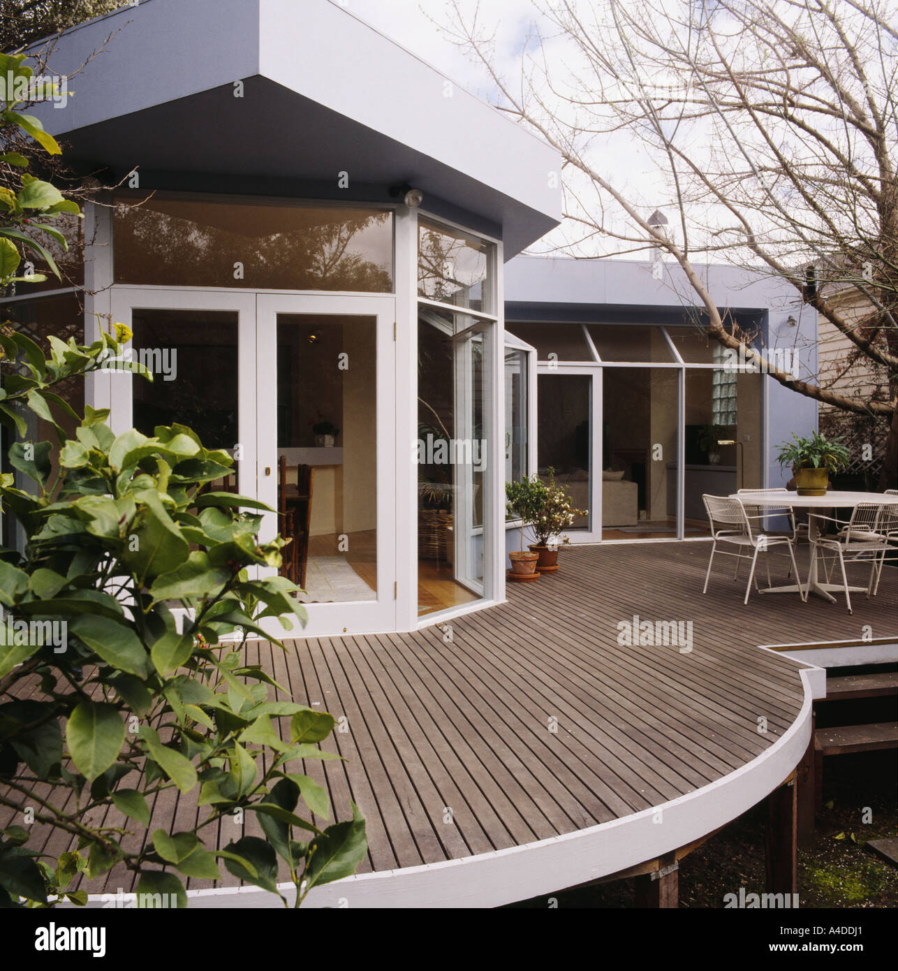 Raised Wooden Decked Terrace And Patio On Modern Single Story Townhouse  With Glass Doors