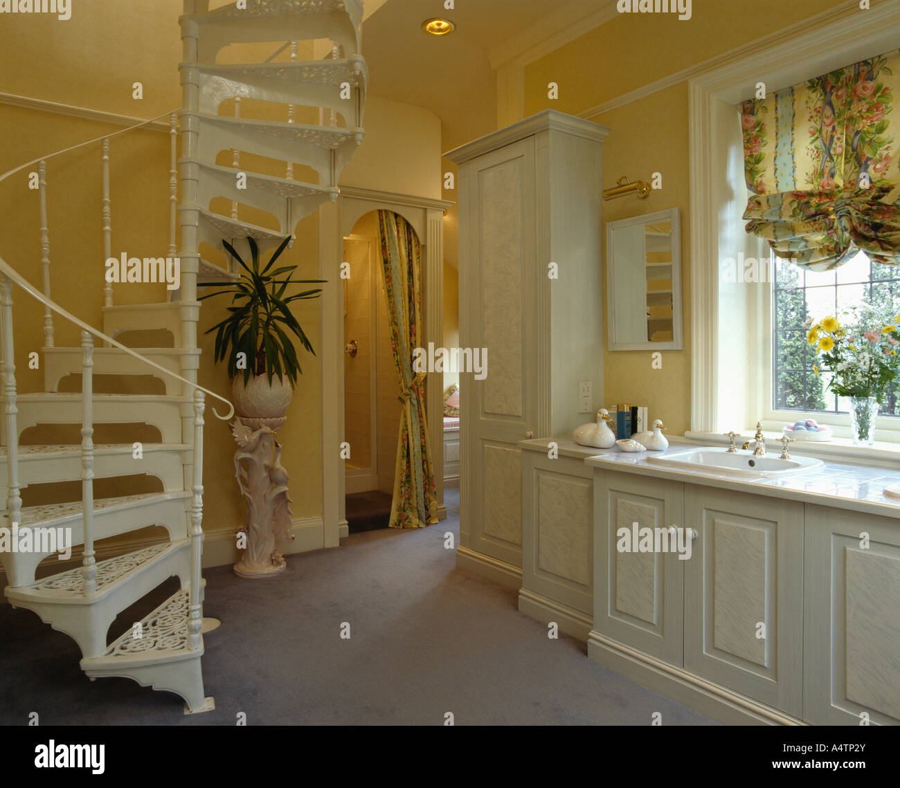 grey and yellow bathroom. Spiral staircase in pale yellow bathroom with grey carpet and built  vanity units